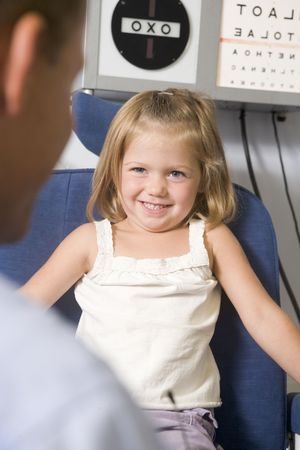 Optometrist in exam room with young girl in chair smiling Stock Photo - 3485444