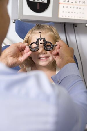 Optometrist in exam room with young girl in chair smiling photo