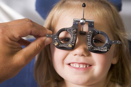 Optometrist in exam room with young girl in chair smiling Stock Photo - 3485598