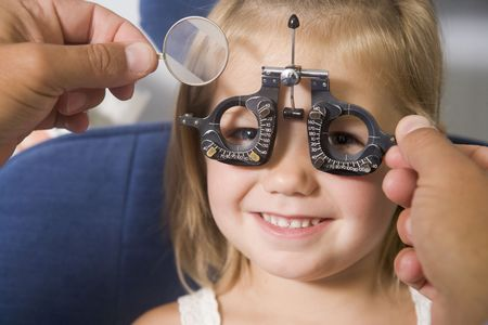 exams: Optometrist in exam room with young girl in chair smiling