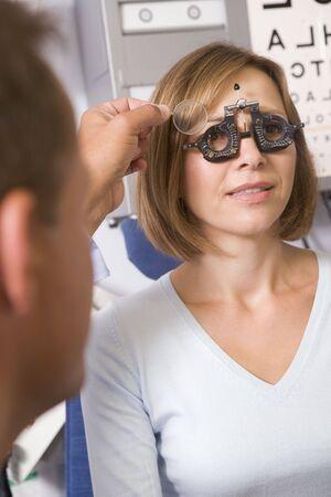 sight chart: Optometrista en la sala de examen con la mujer en silla  Foto de archivo