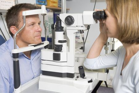Optometrist in exam room with man in chair photo