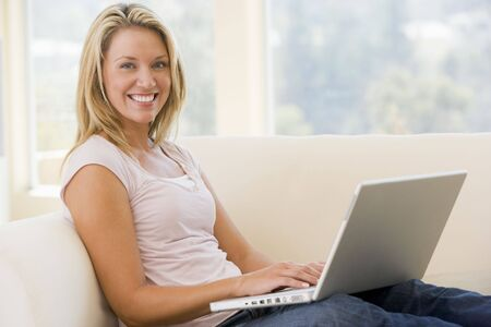early thirties: Woman in living room using laptop smiling