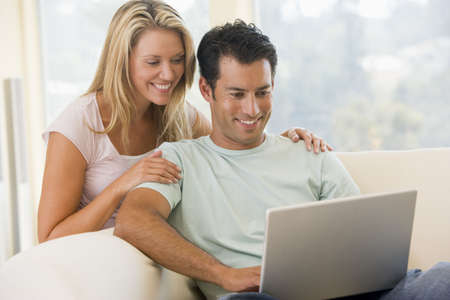 Couple in living room using laptop smiling photo