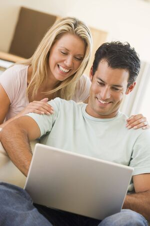 Couple in living room using laptop smiling Stock Photo - 3485290