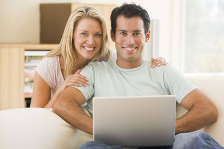 Couple in living room using laptop smiling Stock Photo - 3484690