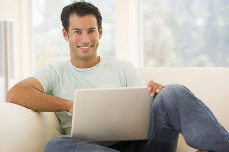 Man in living room using laptop smiling photo