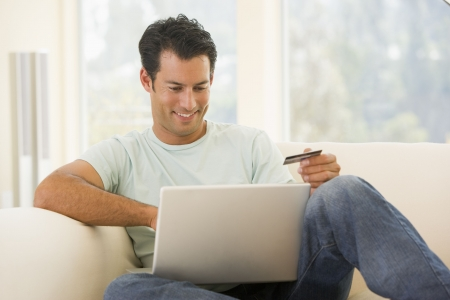 buying online: Man in living room using laptop and holding credit card smiling Stock Photo