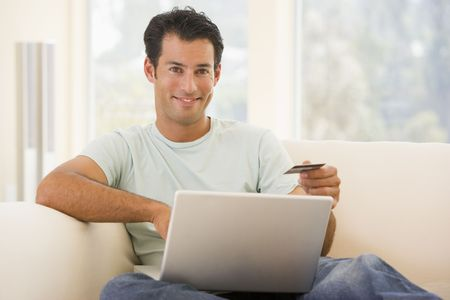 Man in living room using laptop and holding credit card smiling Stock Photo - 3482461