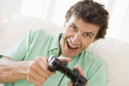 Man in living room playing videogames smiling Stock Photo - 3484778