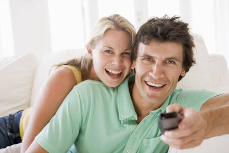 Couple in living room holding remote control smiling Stock Photo - 3485609
