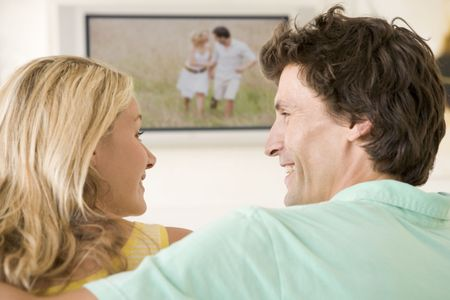 Couple in living room watching television smiling Stock Photo - 3484789