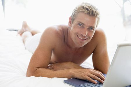 Man lying in bed with laptop smiling photo