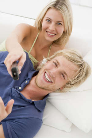 Couple in living room with remote control smiling photo