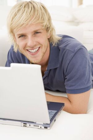 Man in living room with laptop smiling photo