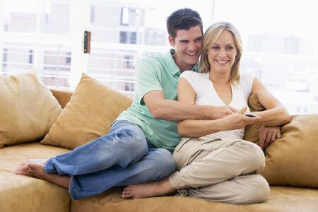couple home: Couple in living room with remote control smiling Stock Photo