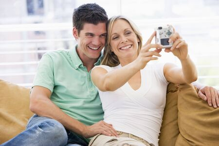 Couple in living room with digital camera smiling photo