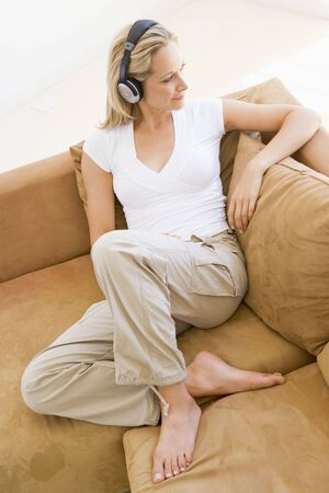Woman in living room listening to headphones smiling Stock Photo - 3485175