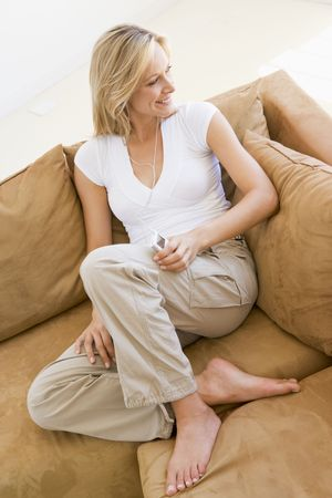 Woman in living room listening to MP3 player smiling Stock Photo - 3485373