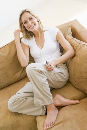 Woman in living room listening to MP3 player smiling Stock Photo - 3485372