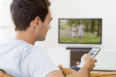 television remote: Man in living room watching television