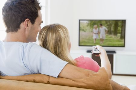 Couple in living room watching television photo
