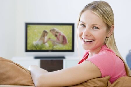 Woman in living room watching television smiling photo