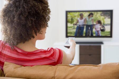 personas viendo television: Mujer en el sal�n viendo la televisi�n Foto de archivo