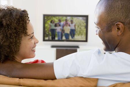 viewing: Coppia in salotto a guardare la televisione sorridente
