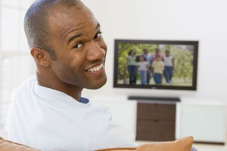 television remote: Man in living room watching television smiling