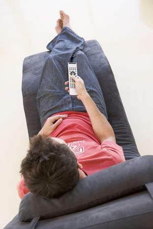 reclining chair: Man sitting in chair using remote control Stock Photo