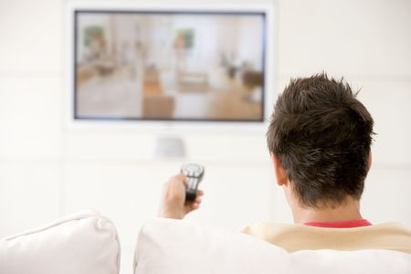 watching tv: Man in living room watching television