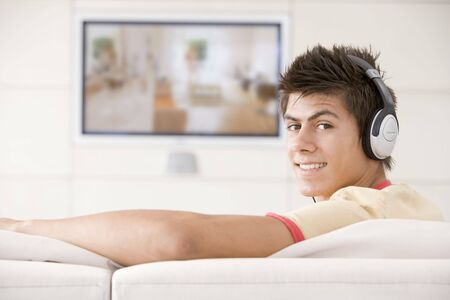 flatscreen: Man in living room watching television and wearing headphones Stock Photo