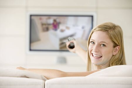 Woman in living room watching television smiling Stock Photo - 3482438