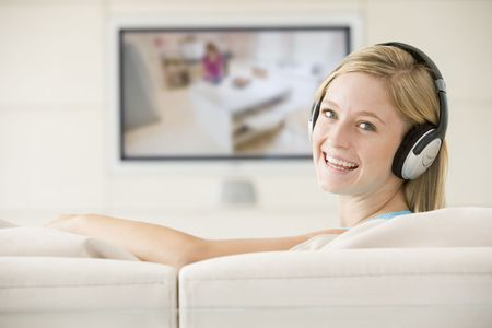 Woman in living room watching television and wearing headphones smiling Stock Photo - 3482410