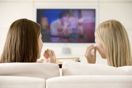 Two women in living room watching television eating chocolates and crying photo