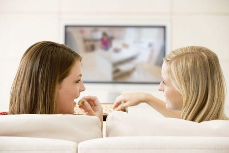 two people talking: Dos mujeres en el sal�n viendo la televisi�n comiendo chocolates sonriente