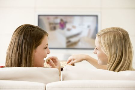 two friends talking: Two women in living room watching television eating chocolates smiling