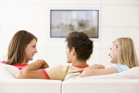 flatscreen: Three friends in living room watching television smiling Stock Photo