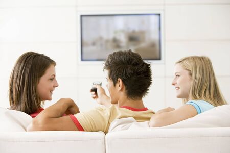 Three friends in living room watching television smiling photo