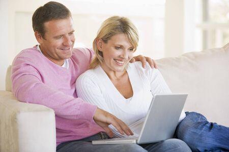coppia in casa: Coppia nel soggiorno con laptop e sorridente