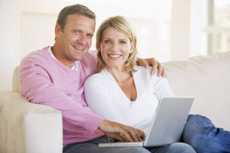 Couple in living room using laptop and smiling photo