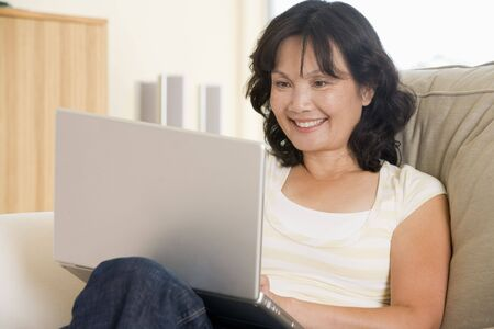 wireless woman work working: Woman in living room using laptop and smiling