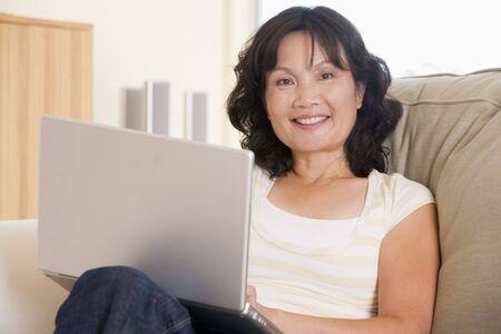 mujeres sentadas: Mujer en el sal�n utilizando port�til y sonriente