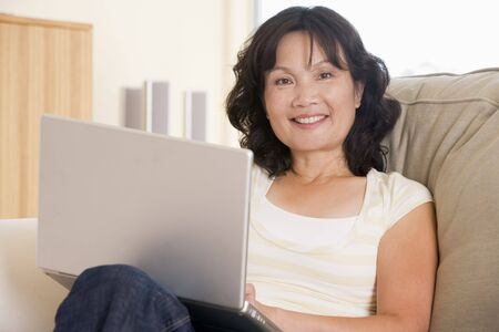 three women: Woman in living room using laptop and smiling