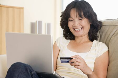 Woman in living room using laptop holding credit card and smiling Stock Photo - 3484530