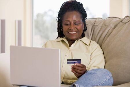 pagando: Mujer en el sal�n port�til usando la celebraci�n de la tarjeta de cr�dito y sonriendo