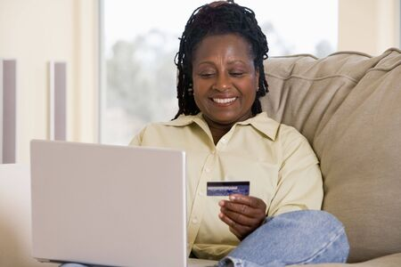 Woman in living room using laptop holding credit card and smiling photo