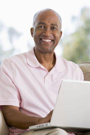 hombre sentado: Hombre en el sal�n utilizando port�til y sonriente Foto de archivo