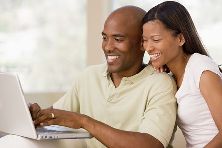 middle age couple: Couple in living room using laptop and smiling